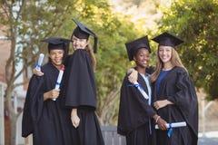 Il ritratto della scuola post-laurea scherza la condizione con il rotolo di grado in città universitaria Immagini Stock