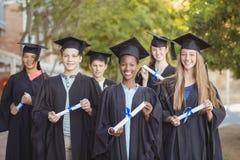 Il ritratto della scuola post-laurea scherza la condizione con il rotolo di grado in città universitaria Fotografia Stock