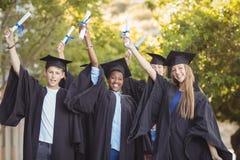 Il ritratto della scuola post-laurea scherza la condizione con il rotolo di grado in città universitaria Immagine Stock