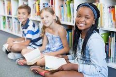Il ritratto della scuola scherza la seduta sul libro di lettura e del pavimento in biblioteca Fotografia Stock