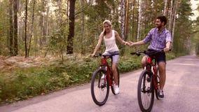 Il ritratto delle coppie felici che si divertono sulla bicicletta guida nel parco dell'estate archivi video