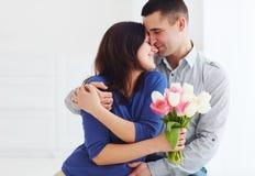 Il ritratto delle coppie felici, il marito e la moglie con la molla fioriscono il mazzo immagine stock