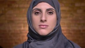 Il ritratto delle mani femminili che fanno il trucco dell'occhio facendo uso della spazzola per la donna musulmana nel hijab sopr video d archivio