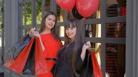 Il ritratto delle ragazze dei clienti, amiche sorridenti alza i sacchetti della spesa su e gode di riusciti acquisti in depositi  video d archivio