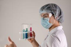Il ritratto dello scienziato nella maschera ed il cappello tengono i tubi del teste e mostrano come su fondo neutrale Concetto di Immagini Stock