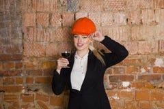 Il ritratto dello studente dell'architetto o il pittore con bicchiere di vino e protegge l'uso del casco Fondo rosso mattone Fotografia Stock Libera da Diritti