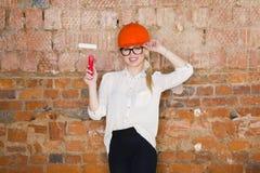 Il ritratto dello studente dell'architetto o il pittore con il rullo di pittura e protegge l'uso del casco Fondo rosso mattone Fotografie Stock