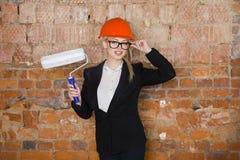 Il ritratto dello studente dell'architetto o il pittore con il rullo di pittura e protegge l'uso del casco Fondo rosso mattone Immagini Stock