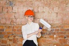 Il ritratto dello studente dell'architetto o il pittore con il rullo di pittura e protegge l'uso del casco Fondo rosso mattone Immagine Stock Libera da Diritti