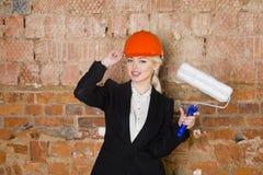 Il ritratto dello studente dell'architetto o il pittore con il rullo di pittura e protegge l'uso del casco Fondo rosso mattone Immagini Stock Libere da Diritti