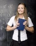 Il ritratto dello studente felice di bellezza con i libri si avvicina alla lavagna Fotografia Stock Libera da Diritti