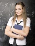 Il ritratto dello studente felice di bellezza con i libri si avvicina alla lavagna Immagine Stock