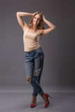 Il ritratto dello studio del modello grazioso della donna con le gambe lunghe del corpo stupefacente che pendono i agains mura i  Immagine Stock