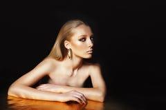Il ritratto di bella donna con capelli biondi e l'oro professionale compongono su fondo nero. Immagine Stock