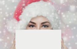 Il ritratto di bella donna in un cappello rosso ed in un maglione rosso tricottato di Santa Claus tiene in sua mano un foglio di  immagine stock libera da diritti