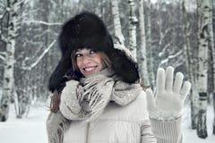 Il ritratto di bella giovane donna che cammina nell'ambito delle precipitazioni nevose dà cinque Fotografie Stock Libere da Diritti