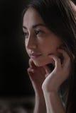 Il ritratto di bella giovane donna guarda fuori la finestra fotografia stock
