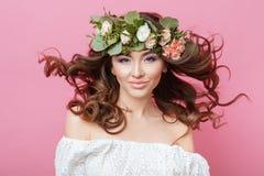 Il ritratto di bella giovane donna sensuale sessuale con pelle perfetta compone il flusso continuo i capelli e dei fiori sulla te fotografia stock libera da diritti
