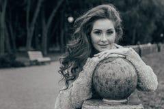 Il ritratto di bella, ragazza dai capelli rossi che la ha pesa gomiti su una palla del granito nel parco, il vento la sviluppa ri fotografia stock