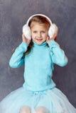 Il ritratto di bella ragazza di risata in una gonna blu e la pelliccia si dirigono Immagine Stock