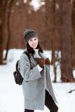 Il ritratto di bella ragazza felice con capelli marroni nella foresta dell'inverno si è vestito in uno stile dei pantaloni a vita fotografie stock