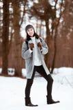 Il ritratto di bella ragazza felice con capelli marroni nella foresta dell'inverno si è vestito in uno stile dei pantaloni a vita immagini stock