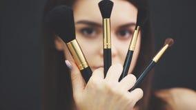 Il ritratto di bella ragazza su un fondo nero con un fronte perfetto con i lotti delle spazzole per trucco la chiude stock footage