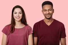 Il ritratto di belle giovani coppie che sembrano sorridenti alla macchina fotografica, sul fondo rosa della parete, porta le magl fotografia stock libera da diritti