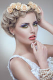 Il ritratto di bellezza della sposa con le rose si avvolge in capelli Immagini Stock Libere da Diritti