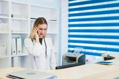 Il ritratto di bello infermiere sorridente alla stazione dello scrittorio mentre parla sul telefono e completare un formulario in fotografia stock libera da diritti
