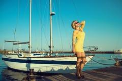 Il ritratto di giallo d'uso sorridente biondo di mezza età splendido della donna stretto-misura il mini vestito e gli occhiali da immagine stock