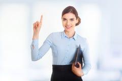 Il ritratto di giovane bella donna di affari sorridente felice che mostra uno sfoglia su, fondo blu Fotografia Stock