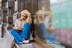 Il ritratto di giovane bella donna ha concentrato il libro di lettura mentre sedendosi sul davanzale del deposito durante il suo  Fotografia Stock Libera da Diritti