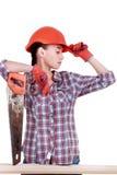 Il ritratto di giovane costruttore femminile in casco con ha visto su bianco Fotografia Stock
