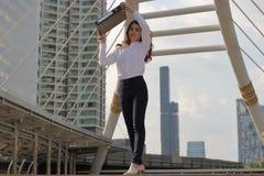 Il ritratto di giovane donna asiatica attraente di affari ha alzato la cartella documenti per luce solare proteggente nel fondo a fotografia stock libera da diritti