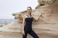 Il ritratto di giovane donna attiva sorride mentre prende la rottura dopo l'allenamento all'aperto in bella natura Immagini Stock Libere da Diritti