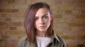 Il ritratto di giovane donna dalla testa Brown attraente che guarda tranquillamente nella macchina fotografica e che distoglie lo video d archivio