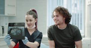Il ritratto di giovane donna del dentista spiegare al suo risultato paziente dei denti esplora i raggi x, uomo paziente ascolta c stock footage