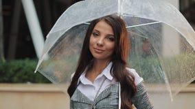 Il ritratto di giovane donna smilling sta con l'ombrello in sua mano sulla via e sull'esaminare la macchina fotografica video d archivio
