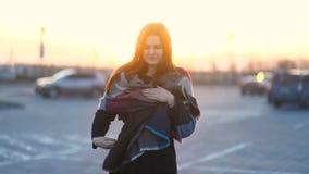 Il ritratto di giovane donna sorridente che cammina verso la macchina fotografica all'aperto, sole è brillante, movimento lento stock footage