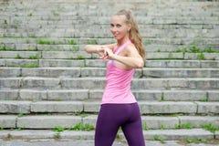 Il ritratto di giovane donna sportiva in vestito da sport fa l'allungamento degli esercizi all'aperto fotografie stock libere da diritti