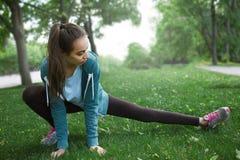 Il ritratto di giovane e donna sportiva in abiti sportivi che fanno l'yoga o che allungano si esercita Immagine Stock