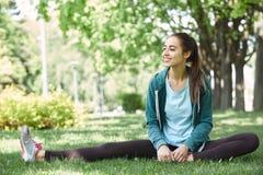 Il ritratto di giovane e donna sportiva in abiti sportivi che fanno l'yoga o che allungano si esercita Fotografia Stock