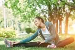 Il ritratto di giovane e donna sportiva in abiti sportivi che fanno l'yoga o che allungano si esercita Immagini Stock
