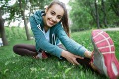 Il ritratto di giovane e donna sportiva in abiti sportivi che fanno l'yoga o che allungano si esercita Immagini Stock Libere da Diritti