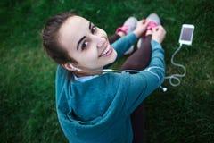 Il ritratto di giovane e donna sportiva in abiti sportivi si trova con lo smartphone sull'erba in parco Immagini Stock