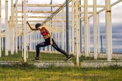 Il ritratto di giovane e donna sportiva in abiti sportivi sta allungando sul percorso Fotografia Stock Libera da Diritti