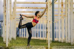 Il ritratto di giovane e donna sportiva in abiti sportivi sta allungando sul percorso Fotografie Stock
