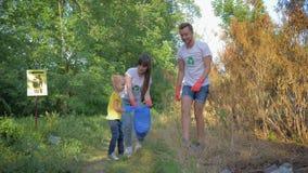 Il ritratto di giovane famiglia felice dei volontari con la ragazza del bambino raccoglie l'immondizia nella borsa di rifiuti men archivi video