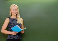 Il ritratto di giovane insegnante con i libri si avvicina alla lavagna Fotografia Stock